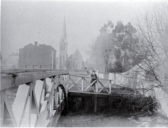 A man stands beside the Worcester Street Bridge : in background is the Cathedral, at left the Providential Society building.