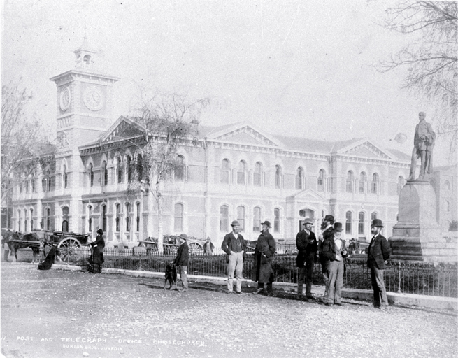 Cathedral Square, showing the Post Office and Godley statue, with delivery carts and pedestrians [ca. 1882] Burton Bros.