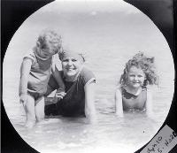 A mother with her two children paddling in the surf, possibly at a Wellington beach [ca. 1900]