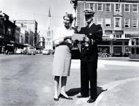 Male and female cabin crew of TEAL standing at the corner of Colombo and Armagh Streets