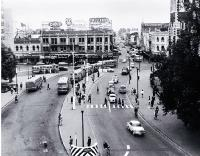 Cars and buses in Cathedral Square : view looking up Colombo Street, with the Colonial Mutual Life building behind the Cathedral