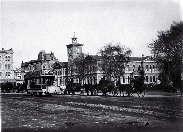 Horse-drawn trams, hackney & hansom cabs in front of the Godley Statue, Cathedral Square, Christchurch : the Post Office is behind.