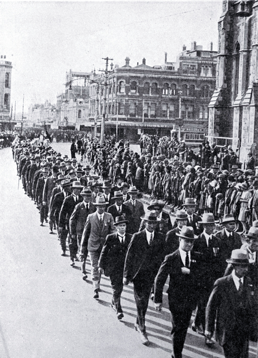 Returned soldiers in mufti and wearing medals marching past the Cathedral, Christchurch [25 Apr. 1926] View catalogue record File Reference CCL PhotoCD 14 IMG0073