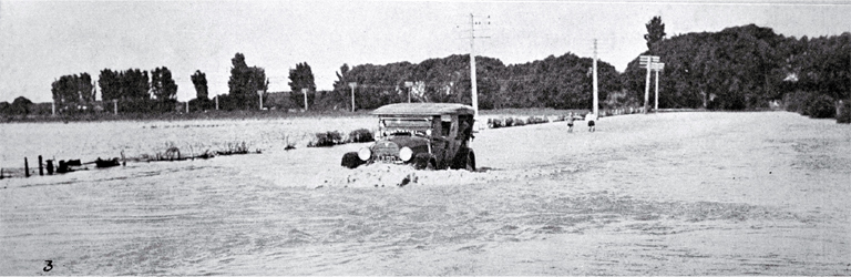 The Waimakariri river breaks its banks again over the main road : a service car negotiates the flooded road.