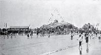 Children paddling near the pier at Cave Rock, Sumner beach, decorated for a summer carnival, Christchurch [1906]