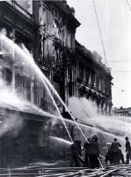 Firemen dampening down the main entrance of Ballantyne's, Colombo Street, Christchurch