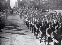 Second echelon of New Zealand Expeditionary Forces march west along Cashel Street, under the Bridge of Remembrance