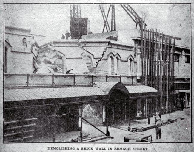 Demolishing a brick wall, T. Armstrong & Co. premises, corner of Colombo and Armagh Streets