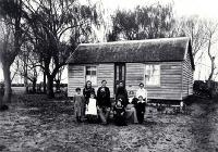 The family of Arthur John Inwood (1850-1932) and his wife Angelina (1860?-1919) pictured outside their dwelling