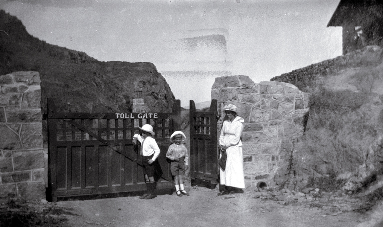 A woman with children stands outside the toll-gate to the Summit Road leading past the Sign of the Kiwi, Port Hills, Christchurch