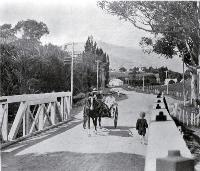 Horse and buggy crossing the bridge : looking up towards the Wairewa Valley from Little River, Banks Peninsula. [1925]