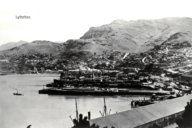 Lyttelton Harbour with ships at dock and tugboat on the water [191-?]