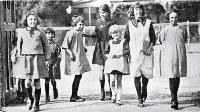 Photograph of Girls merrily on their way to Phillipstown School on the day Christchurch schools reopened after five months due to the removal of restrictions on the assembly of children after the end of the infantile paralysis epidemic.[1925]]