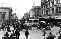Cars, bicycles and a bus create a busy scene at the Bank corner, Christchurch : Barnett & Co. Chemists in the foreground.