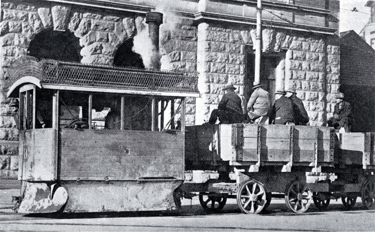 A Kitson steam tram runs past the Government Buildings in Cathedral Square with tramways workers on board