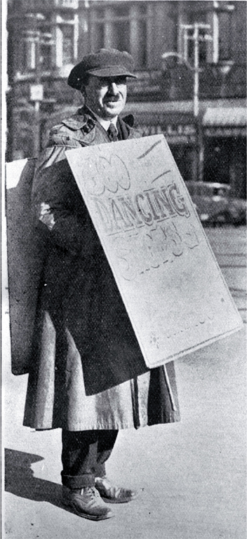 A sandwich-board man advertising dancing shoes in Cathedral Square, Christchurch