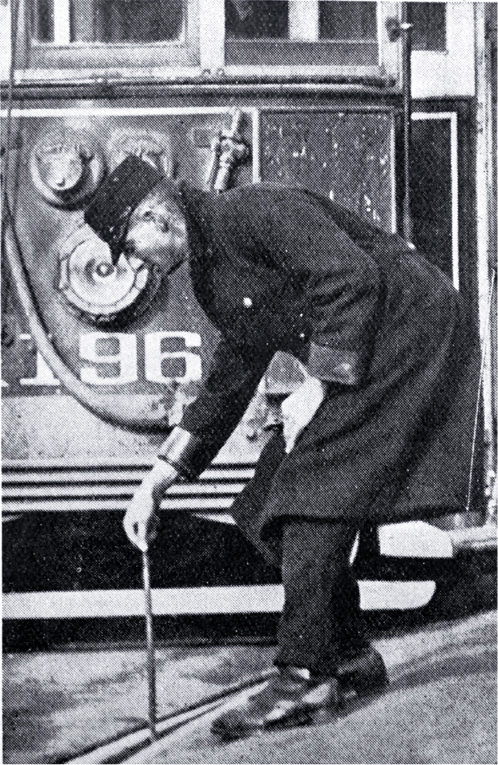 A tram conductor changes the points of the tram rails with a point bar