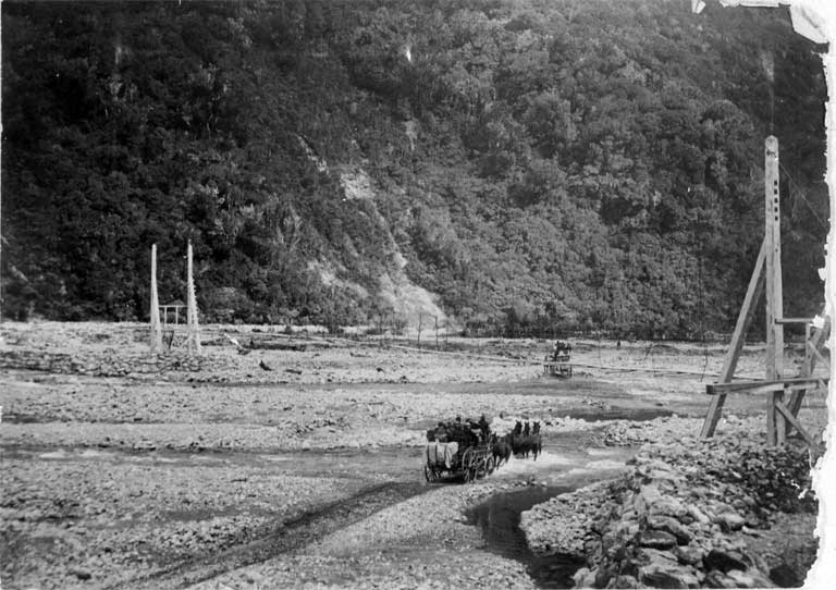Coaches shown passing under a swing bridge, crossing possibly the Otira River between Otira and Aickens.
