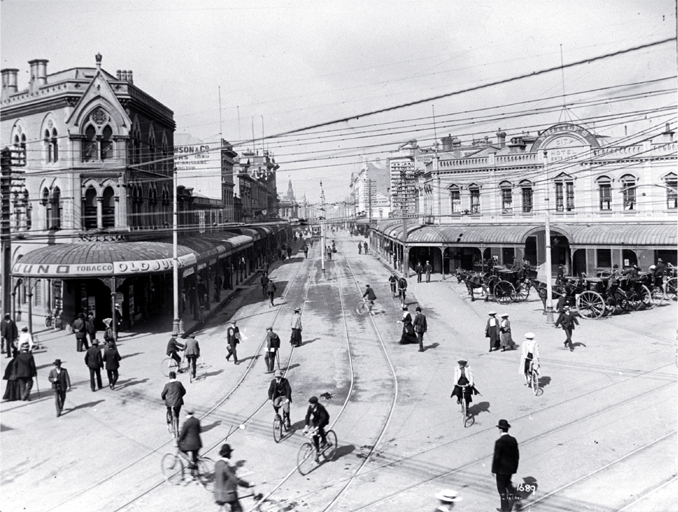 Looking down High Street while cyclists cross the intersection of Colombo and Hereford Streets. Circa 1910 Christchurch City Libraries File Reference CCL Photo CD 1, IMG0002