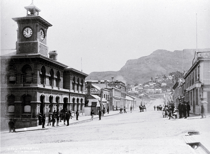 The Post and Telegraph Office in Norwich Quay, Lyttelton [ca. 1885] The Office was built in 1876. In the background are the offices of the New Zealand Shipping Company and the shop of R. Forbes, ship chandlers.  CCL PhotoCD 2, IMG0009
