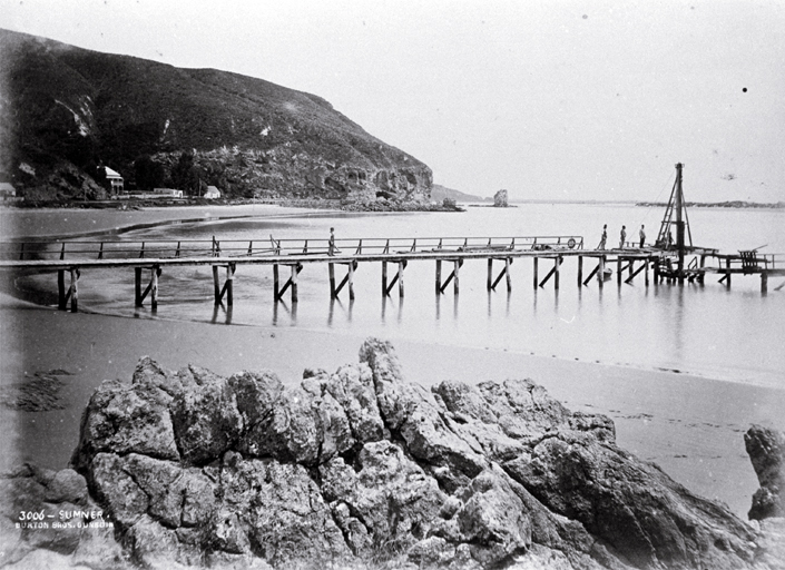 Construction of the Sumner Pier, Christchurch : looking from Cave Rock past the Sumner Hotel to Clifton Spur and Shag Rock.